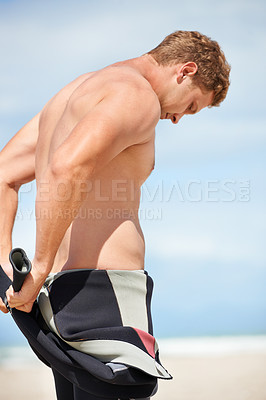 Buy stock photo A handsome surfer putting on his wetsuit on the beach