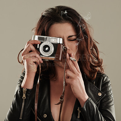 Buy stock photo A young woman snapping pictures while smoking a cigarette