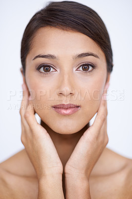 Buy stock photo A gorgeous young woman feeling her smooth, soft skin in a studio shoot