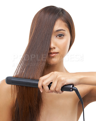 Buy stock photo A young woman straightening her hair