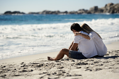 Buy stock photo A couple sitting on the beach looking at the ocean