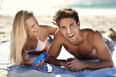 Buy stock photo A young couple applying sunscreen at the beach