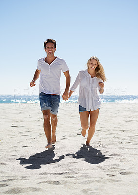 Buy stock photo A happy couple running on the beach
