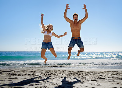 Buy stock photo A young couple jumping into the air while enjoying a day on the beach
