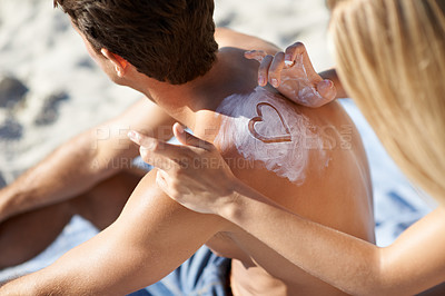 Buy stock photo A young woman making a heart shape with sunscreen on her boyfriend's back