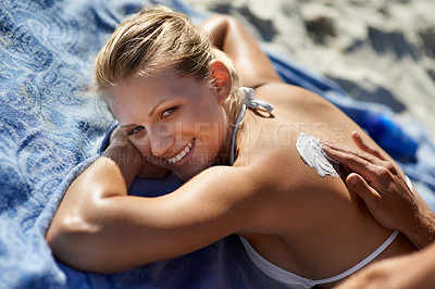 Buy stock photo A beautiful woman lying on the beach while someone puts sunscreen on her back