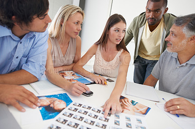 Buy stock photo A group of designers choosing images around a boardroom table