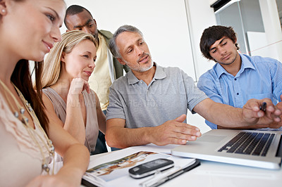 Buy stock photo A group of business people sitting around a boardroom tableShot of two coworkers going over paperwork in an office