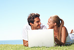 Cute couple using laptop outdoors