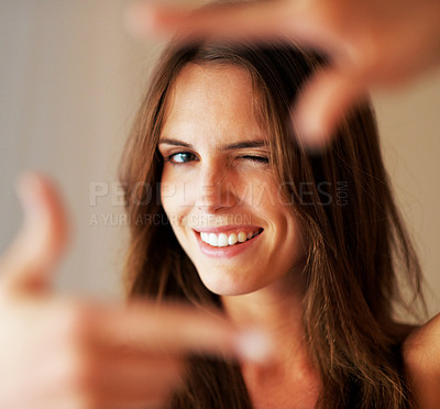 Buy stock photo Young woman creating a frame with her hands and smiling at you