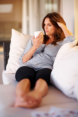 Buy stock photo An attractive young lady relaxing on sofa with cup