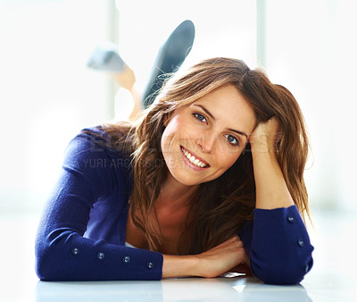 Buy stock photo Portrait of relaxed young woman lying on the floor smiling engagingly at you - copyspace