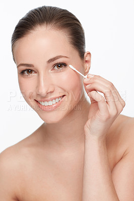 Buy stock photo Cropped view of a young woman using an earbud to clean her skin around the eye