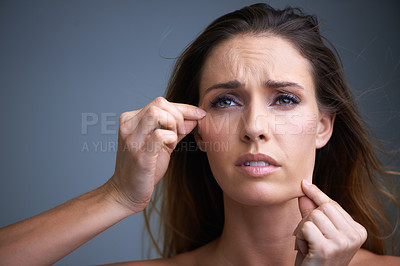 Buy stock photo An attractive young woman looking disappointed while pulling on her skin