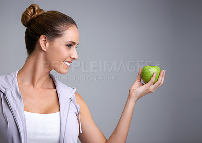 Buy stock photo Profile of an attractive young woman holding a green apple
