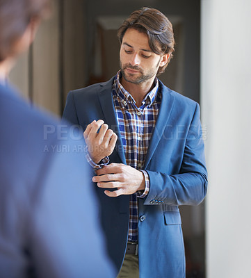 Buy stock photo Shot of a handsome man getting ready for work