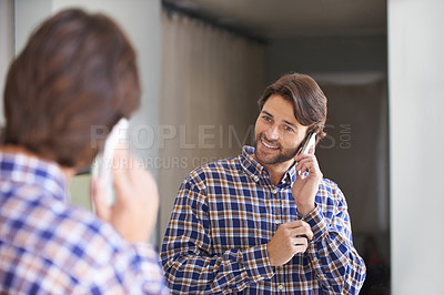 Buy stock photo Shot of a handsome man talking on the phone while getting ready for work