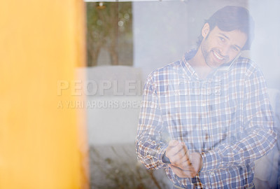 Buy stock photo Through the glass shot of a handsome man getting dressed while talking on the phone