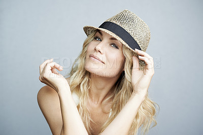 Buy stock photo Studio portrait of an attractive woman wearing a straw hat