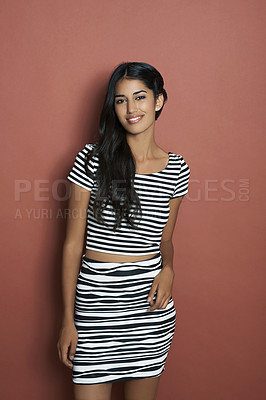 Buy stock photo Studio shot of a beautiful Indian model standing in front of a brown background and smiling at the camera