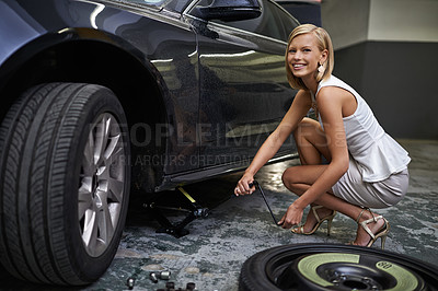 Buy stock photo A gorgeous woman using a jack to lift her car while changing a tyre