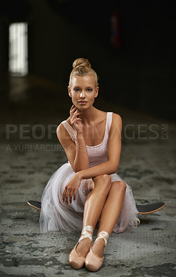 Buy stock photo A young ballerina sitting on a skateboard in a basement and smiling at the camera
