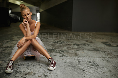 Buy stock photo A young ballerina sitting on her skateboard wearing sneakers