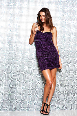 Buy stock photo Full length shot of a stylishly dressed young woman standing against a tiled wall and drinking champagne