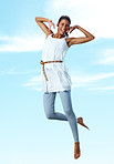Casual woman jumping in joy against sky