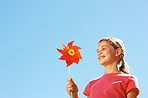 Cute young girl with a pinwheel, blue sky as the background
