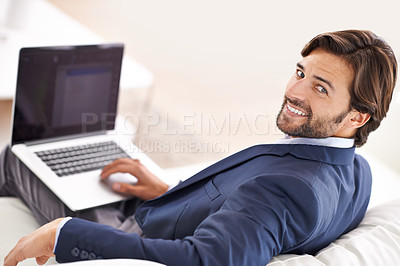 Buy stock photo An attractive businessman reclining on the couch while working on his laptop