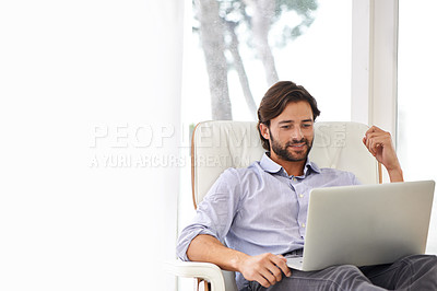 Buy stock photo A handsome businessman working on his laptop