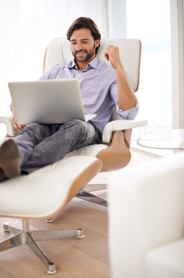 Buy stock photo A handsome businessman relaxing while working on his laptop