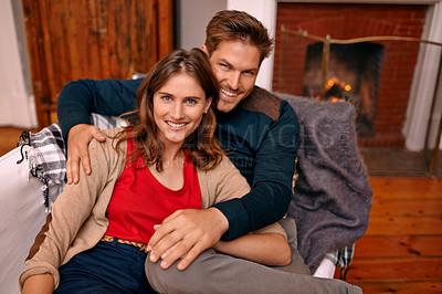 Buy stock photo A young couple relaxing on a couch by the fireplace