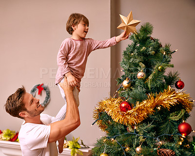 Buy stock photo A father lifting his son to put the star on the Christmas tree