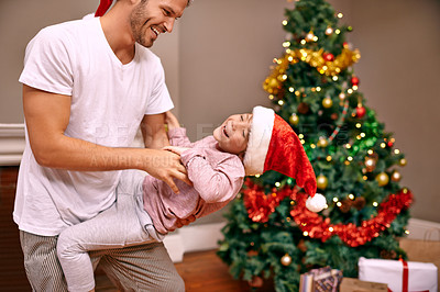 Buy stock photo A father tickling his son next to a christmas tree