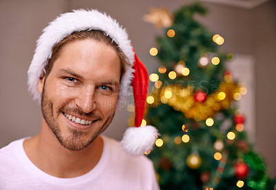 Buy stock photo A handsome man wearing a christmas hat smiling at the camera with a decorated tree in the background