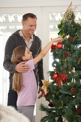 Buy stock photo A young girl decorating a christmas tree with her father