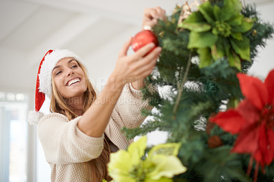 Buy stock photo An attractive woman decorating her christmas tree while at home