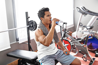 Buy stock photo A young ethnic man sitting on a weight bench and drinking water