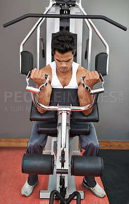 Buy stock photo Full-length shot of a young ethnic man exercising in the gym
