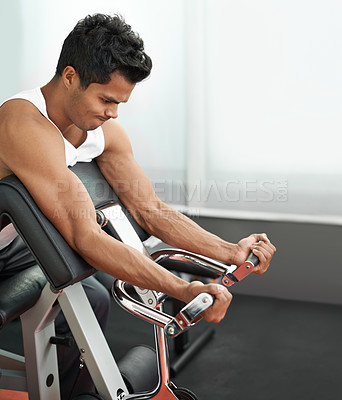 Buy stock photo A young ethnic man working out his arm muscles