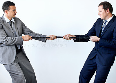 Buy stock photo Two businessmen involved in a tug-of-war while wearing suits and isolated on white
