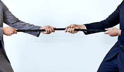 Buy stock photo Cropped studio shot of two men pulling on the same rope