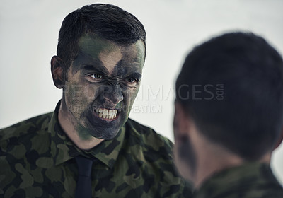 Buy stock photo A military man with his face camouflaged making a mean face while looking in the mirror