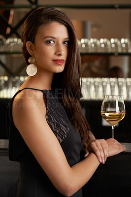 Buy stock photo An attractive and classy young woman standing at the bar of a upper class establishment