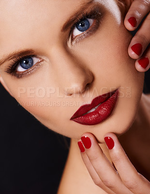 Buy stock photo Cropped image of a woman wearing red lipstick looking at the camera with fingers with red polish touching her face