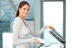 Pretty businesswoman making copies on the photocopy machine