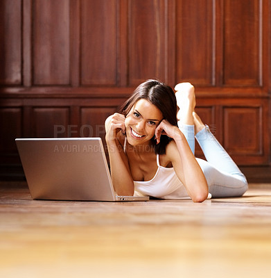 Buy stock photo Relaxed young lady lying on floor with laptop