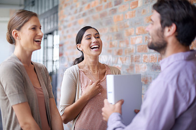 Buy stock photo Shot of a coworkers talking to each other in a office hallway